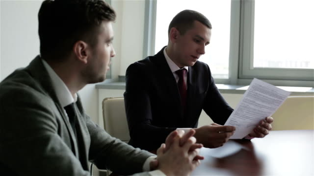 Two businessmen in suits are sitting at a table in front of the window and learning a new contract. video