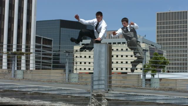 zwei geschäftsleute springen über schranke, zeitlupe - stuntman stock-videos und b-roll-filmmaterial