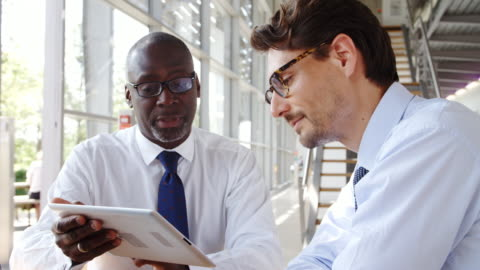due uomini d'affari che guardano il tablet digitale durante l'incontro intorno al tavolo in ufficio moderno - due persone video stock e b–roll