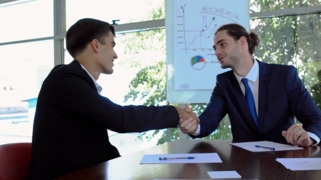 Two businessmen makes a deal in the office video