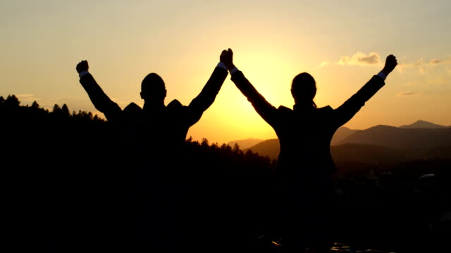 close up: two businessmen on the top of skyscraper with hands raised at sunset - sezione superiore video stock e b–roll