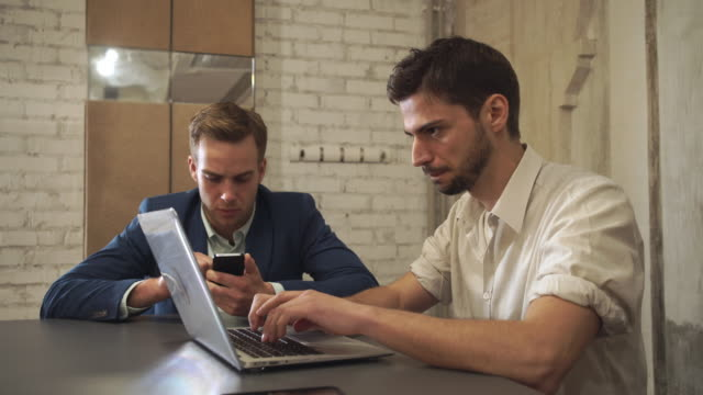 Two businessmen read news and chatting in social networking service on modern gadget video