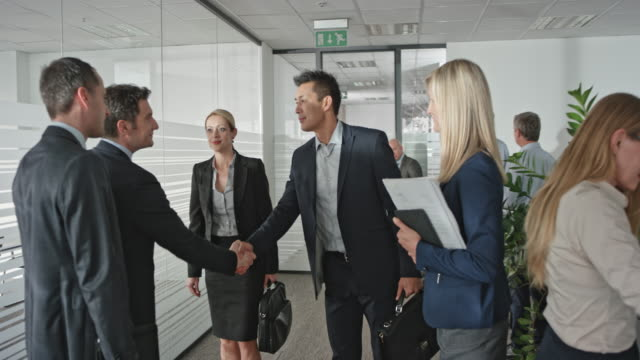two businessmen shaking hands with a businesswoman and an asian businessman before they enter the meeting room. - деловая встреча стоковые видео и кадры b-roll