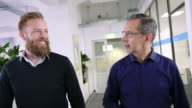 istock Two businessmen talking while walking in office 1176752673