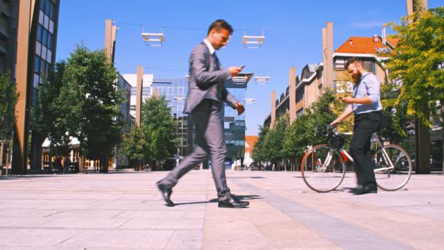 slo mo två affärsmän använder mobiltelefoner medan promenader i staden - kostym sida bildbanksvideor och videomaterial från bakom kulisserna