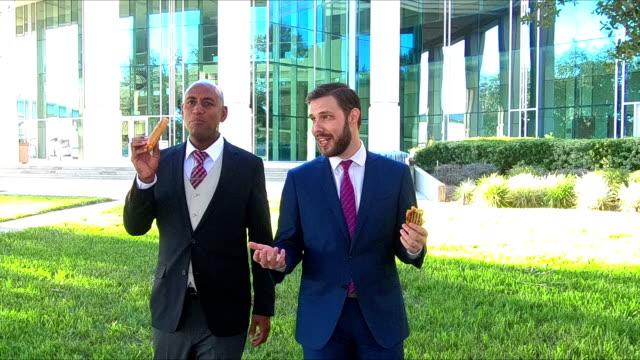 Two businessmen walking, talking, eating lunch video