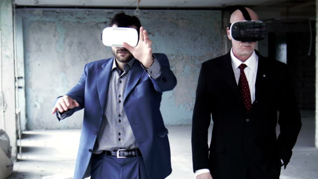 Two businessmen wearing on vr goggles and talking video
