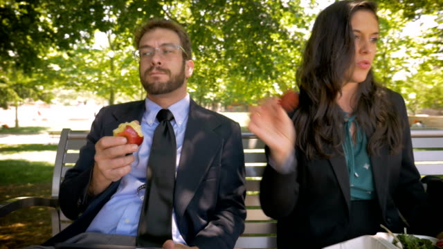 Two businesspeople dancing while sitting and eating healthy food for lunch Two happy attractive millennial 30s businesspeople silly dancing while sitting with a digital tablet and eating healthy whole organic food for lunch outside on a park bench in slow motion mid adult stock videos & royalty-free footage