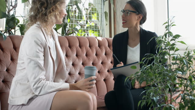 Two businesswoman talking at sofa