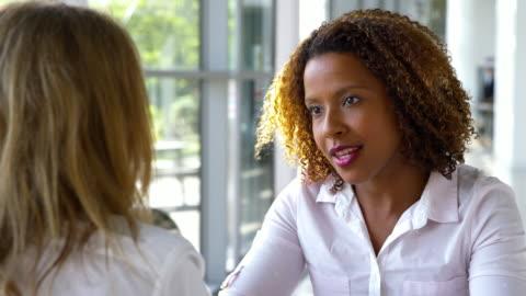 due imprenditrici che si incontrano attorno a un tavolo in ufficio moderno - due persone video stock e b–roll