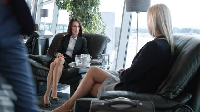 DS Two businesswomen talking in the business lounge at the airport Wide dolly shot of two Caucasian businesswomen talking as they sit in the business lounge at the airport. Shot in Slovenia. cross legged stock videos & royalty-free footage