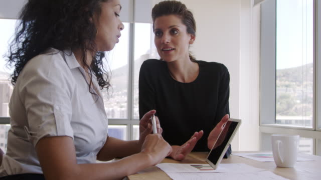 Two Businesswomen Using Digital Tablet In Office Meeting