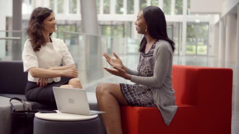 due imprenditrici che lavorano nella hall dell'ufficio moderno - due persone video stock e b–roll