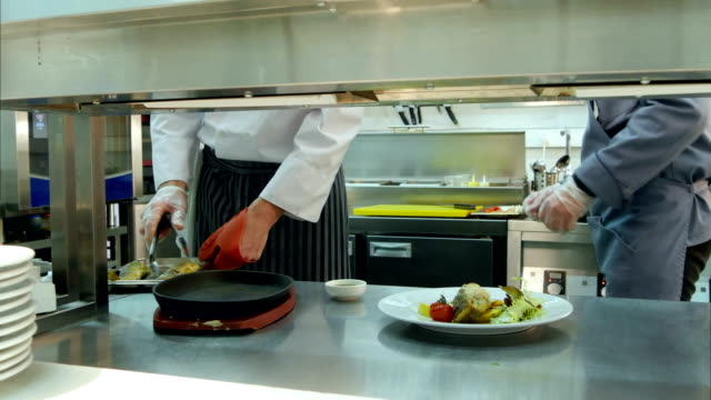 two busy cooks at work cooking in the restaurant kitchen - busy restaurant kitchen stock videos & royalty-free footage