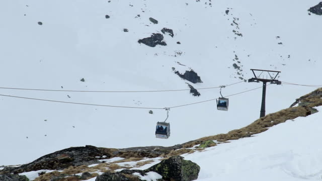 Two cable cars moving in opposite directions above rocky mountains, video