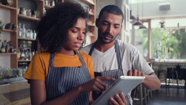 stockvideo's en b-roll-footage met twee cafe business partners met behulp van digitale tablet - een tablet gebruiken