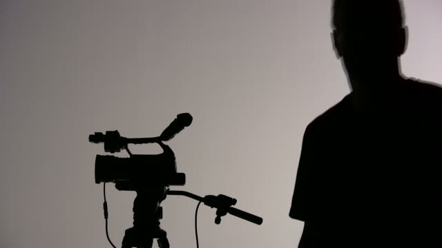 (HD1080i) Two Cameramen; Videographers Work, Share Camera, Directs; Silhouette video