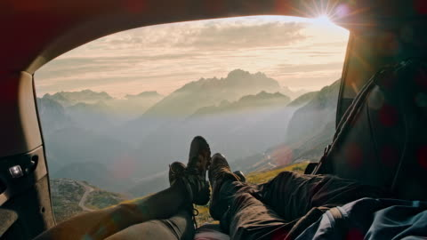 MS Two campers resting in the trunk of the car in mountains Medium shot of two campers resting in the trunk of the car in mountains at sunset. Low angle shot of their feet. Mangart or Mangrt is a mountain in the Julian Alps, located on the border between Italy and Slovenia. Shoot in 8K resolution. 10 seconds or greater stock videos & royalty-free footage