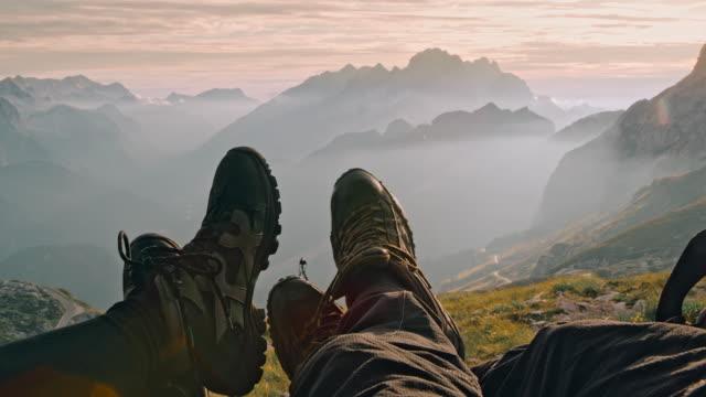 vidéos et rushes de ms deux campeurs se reposant dans leur tente dans les montagnes - se reposer