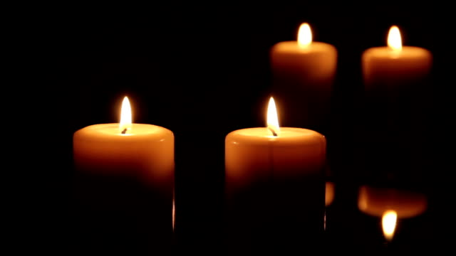 Two candles burning in front of a mirror video