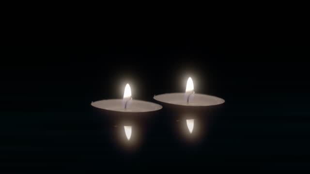 Two candles floating on water surface burn in dark. video