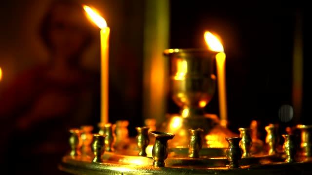 due candele in chiesa su un candelabro - candeliere video stock e b–roll