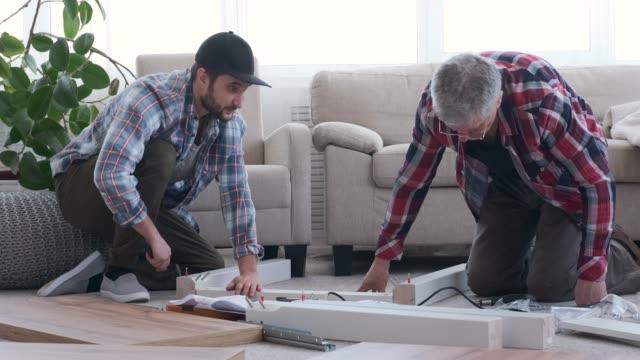 Two carpenter assembling furniture at home