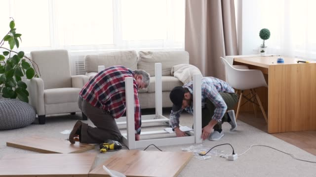Two carpenter assembling table at home