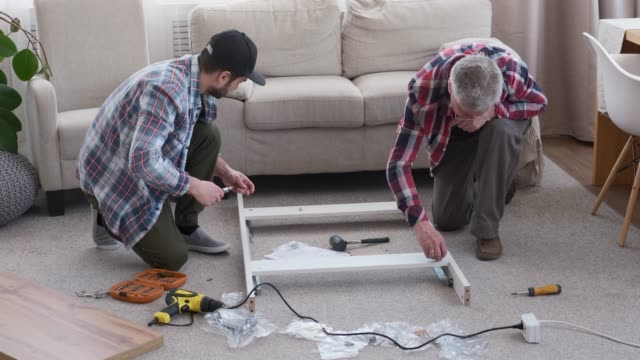 Two carpenters assembling furniture at home