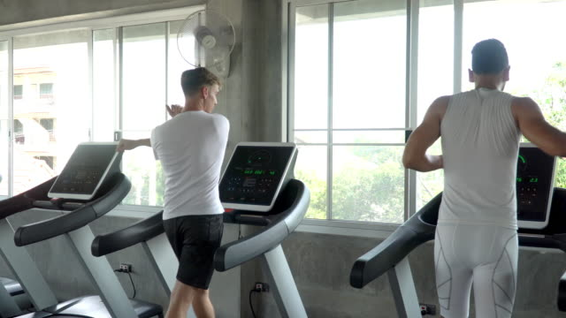 4k two caucasian athletic man friend in sport clothing warm up exercises before running on treadmill in gym. sportsman do jogging workout training in fitness club. strong healthy lifestyle concept. - runner rehab gym video stock e b–roll