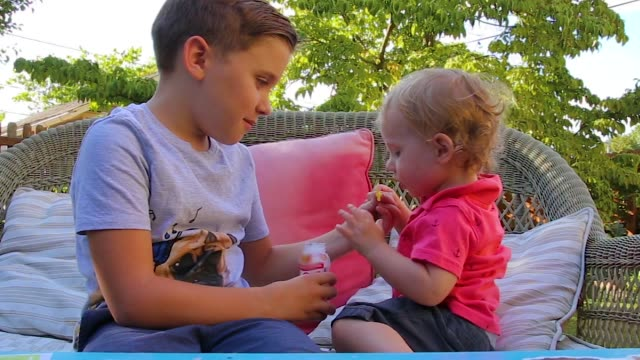 Two Caucasian boys blow bubbles together on the lawn in their backyard during Summer Two Caucasian boys blow bubbles together on the lawn in their backyard during Summer cousin stock videos & royalty-free footage