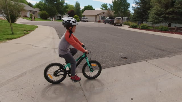 Two Caucasian Boys (Five Years-Old and Four Years-Old) Wearing Bike Helmets Cross the Street as They Ride their Bikes through a Residential Neighborhood under a Partly Cloudy Sky