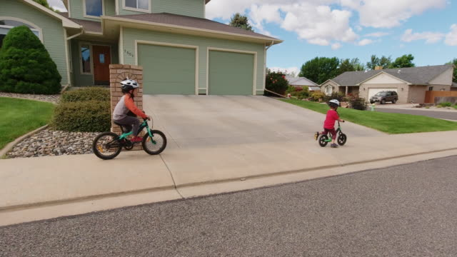 Two Caucasian Boys (Five Years-Old and Four Years-Old) Wearing Bike Helmets Ride their Bikes through a Residential Neighborhood under a Partly Cloudy Sky