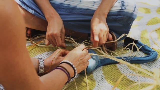 två kaukasiska honor vävning korg på hantverk verkstad tillsammans. närbild video av kvinnors händer att göra hantverk. - halmslöjd bildbanksvideor och videomaterial från bakom kulisserna