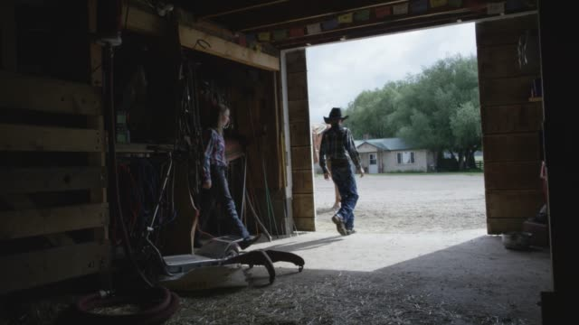 Two Caucasian Kids Walk out of a Stable A white boy and a white girl walk out of a stable together on a farm under a cloudy sky. cowgirl stock videos & royalty-free footage