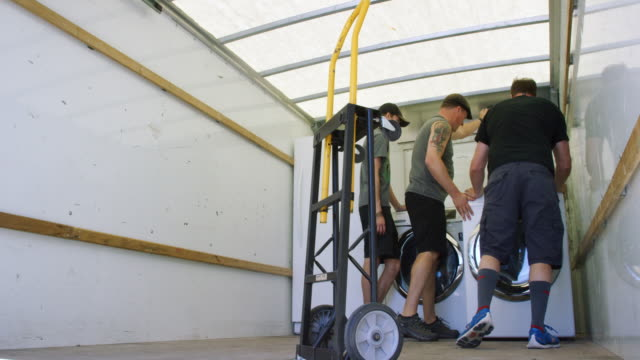 Two Caucasian Man and a Caucasian Boy in His Late Teens Position a Clothes Washer in Place Next to a Dryer in the Back of a Moving Truck