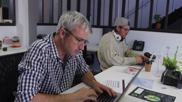 vídeos de stock e filmes b-roll de two caucasian men working in a creative office - envolvimento dos funcionários