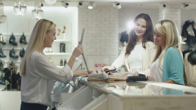 Two cheerful girls are checking out at a cash desk in a department store.