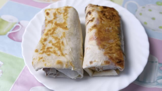 Two chicken homemade shawarma on the white plate.