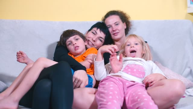 Two children and two women are hugging on the couch.