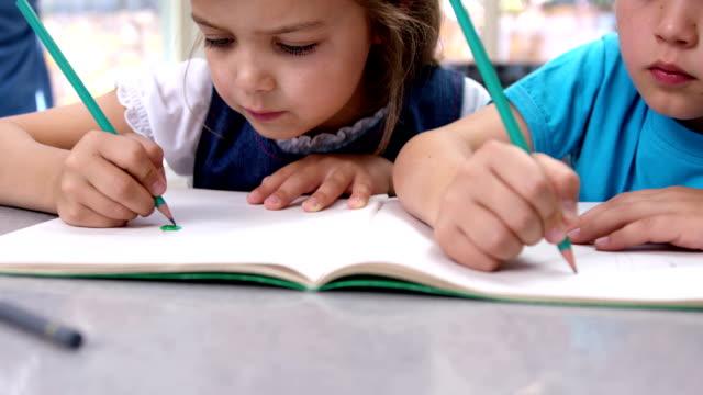 due bambini sono da colorare - fianco a fianco video stock e b–roll