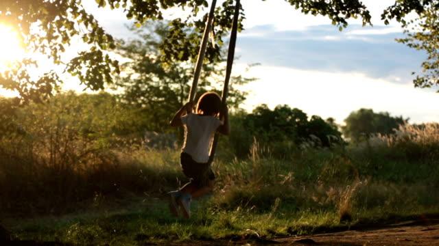 vídeos de stock, filmes e b-roll de dois filhos, irmãos do rapaz, se divertindo em um balanço no quintal na sunset - paraquedismo