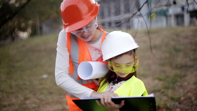 Two children girls in construction helmets looking at white sheet of paper or drawing and smiling
