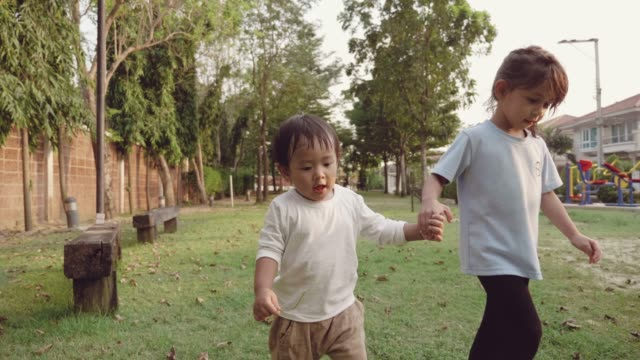 two children holding hands, walking together outdoors - brother stock videos and b-roll footage