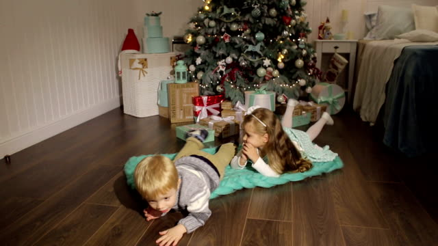 Two children lie on the floor near Christmas tree. video