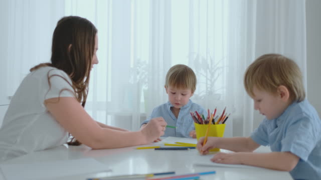 two children of boys draw with his mother sitting in the kitchen. happy family at home - matita colorata video stock e b–roll