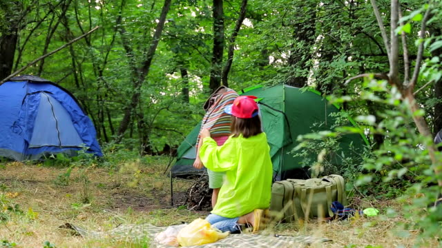 Two children play in the clearing near the tents in the forest. video