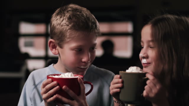 vídeos de stock, filmes e b-roll de duas crianças brincando de beber chocolate quente junto - chocolate quente
