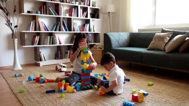 två barn som leker med leksak block. - konst och konshantverk bildbanksvideor och videomaterial från bakom kulisserna