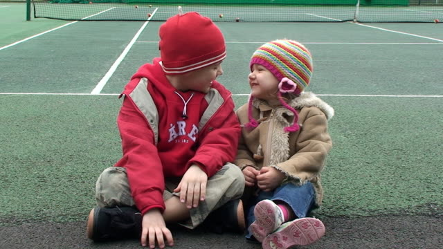 Two children sitting on tennis court video